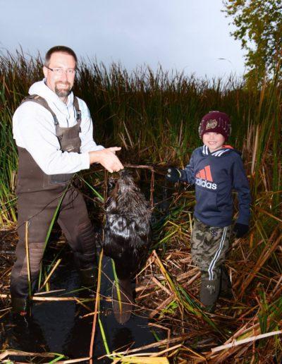 Darrell Schreiber teaching Levi Budke how to trap beaver.